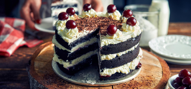 Urodzinowy tort czekoladowo-śmietankowy z wiśniami i bitą śmietaną